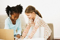 Two girls (4-6) opening large box in living room, smiling