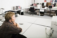 Man sitting with arms folded on desk in office
