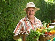 Mature man holding basket of vegetables in garden, portrait