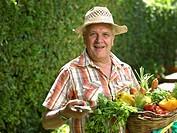 Mature man holding basket of vegetables in garden, portrait