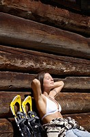 Young woman, sunbathing in front of alpine hut
