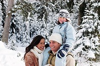 Familiy in snow-covered forest