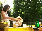 Woman handing plate to girl (4-6) by dinner table, outdoors