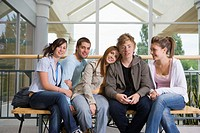 Group of teenagers (15-17) in shopping centre, smiling, portrait