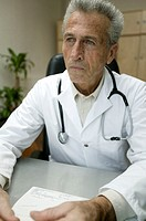 Senior male doctor at desk, stethoscope around neck, looking away