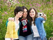 Three young women in field, taking self portrait, smiling