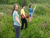 Young women standing in field, one reading map, portrait