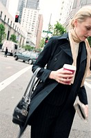 Woman in city street, holding a coffee cup