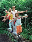 Multi generational family balancing on log in forest, smiling
