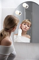 Young woman checking appearance in mirror (focus on reflection)