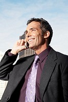 Mature businessman talking on cell phone, smiling