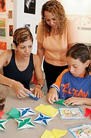 Family Day, origami program, Hispanic boy, teacher, mother. ArtCenter South Florida. Lincoln Road. Florida. USA.