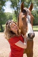 Woman patting American Quarter horse, outdoors