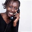 Woman holding telephone receiver, smiling, portrait