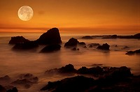 Moonset over rocky shore in Laguna Beach California
