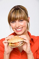 Young woman holding hamburger, smiling, portrait, close-up