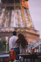Couple on Seine River houseboat under Eiffel Tower for romantic sunset