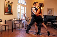 Couple tango dancing in Buenos Aires cafe to accordian music