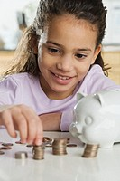 Young Girl with Piggy Bank and Stacks of Coins