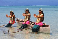 Three Polynesian girls on outrigger canoe in Aitutaki lagoon