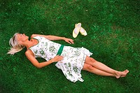 Blond woman lying on grass in summer dress