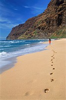 Polynesian woman running on white sandy beach at Polihale on Island of Kauai Hawaii