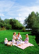 Family of four having summer picnic in Swedish countryside