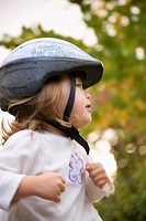 Profile shot of young girl wearing a bike helmet with trees in the background