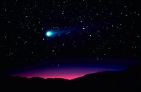 View of Comet Hyakutake over a mountain range with a starry sky in the background
