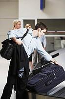Man Retrieving Luggage at Baggage Claim
