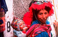 A woman wearing colorful clothing carrying a child on her back at Pisac market near Ollantaytambo, Peru