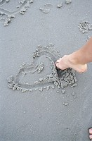 A person uses their toes to draw a heart shape in the wet sand at a beach