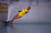 Water-skiing woman sends up a wide plume of water behind her as she goes into a turn