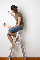 Young Woman Sitting on Ladder Holding Paint Sample to Wall