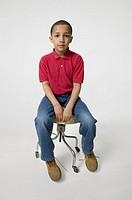 Boy (6-7) sitting on swivel chair in studio, portrait,