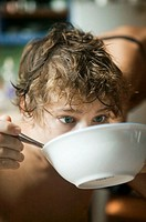 Teenage boy (16-17), eating from bowl in kitchen