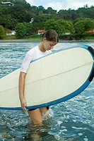 Young woman carrying surfboard in ocean