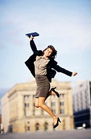 Businesswoman leaping in city