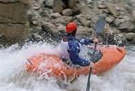 Kayaker racing in white water, side view (blurred motion)