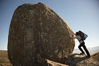 Man with Backpack Pressing Against Boulder (thumbnail)