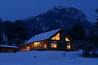 Log cabin at night in the snow. Property released.