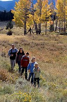 A family of five hiking on a meadow trail in single file during fall in Rocky Mtn Nat´l Park, CO.