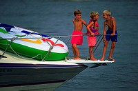 Young boys interacting socially on a family boating outing.  Three young friends in a peaceful moment during a day of fun on the Chesapeake Bay.(Peopl...