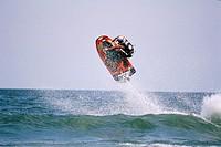 Man riding jetski over wave.