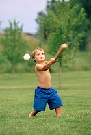 Young boy wearing only a pair of blue shorts playing baseball while out on the field.