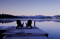 Two empty deck chair sit on dock at sunrise by Mirror Lake, Lake Placid, NY overlooking trees, hills and lakeside resort.
