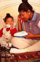 One-year-old African American girl playing telephone with her mother.