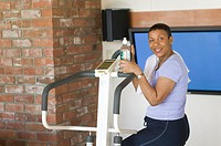 Senior, African American, exercising on stepper machine and plasma TV  MR-0510 PR-0505