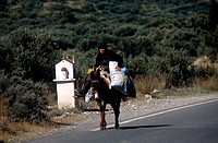 Senior woman riding a donkey, Crete, Greece