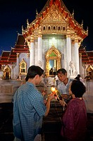 Young men and a mid adult woman lighting candles in front of a temple, Wat Benchamabophit, Bangkok, Thailand